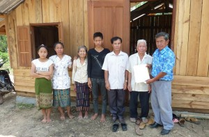 Mr Khamkhone Phaioudone, (President of QLA's Board) hands over the house to Vanh and the village authorities.